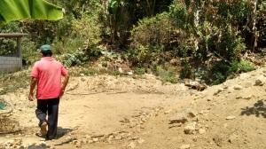 """Un familiar de doña Mary camina sobre el terreno donde estaba la casa de la fémina que fue aplastada totalmente por la tierra de un cerro que desgajó hace año y medio ante el paso de la tormenta """"Manuel"""", en el pueblo de San José Vista Hermosa, municipio de Iliatenco en la Montaña de Guerrero."""